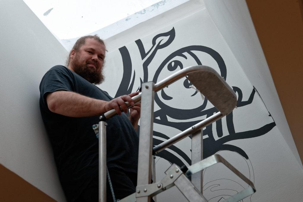 Sarjakuvataiteilija ja kuvittaja Petteri Tikkanen maalaamassa seinätaideteosta kirjaston monitoimitilaan. Tilan avajaisia vietetään kirjan ja ruusun päivänä.