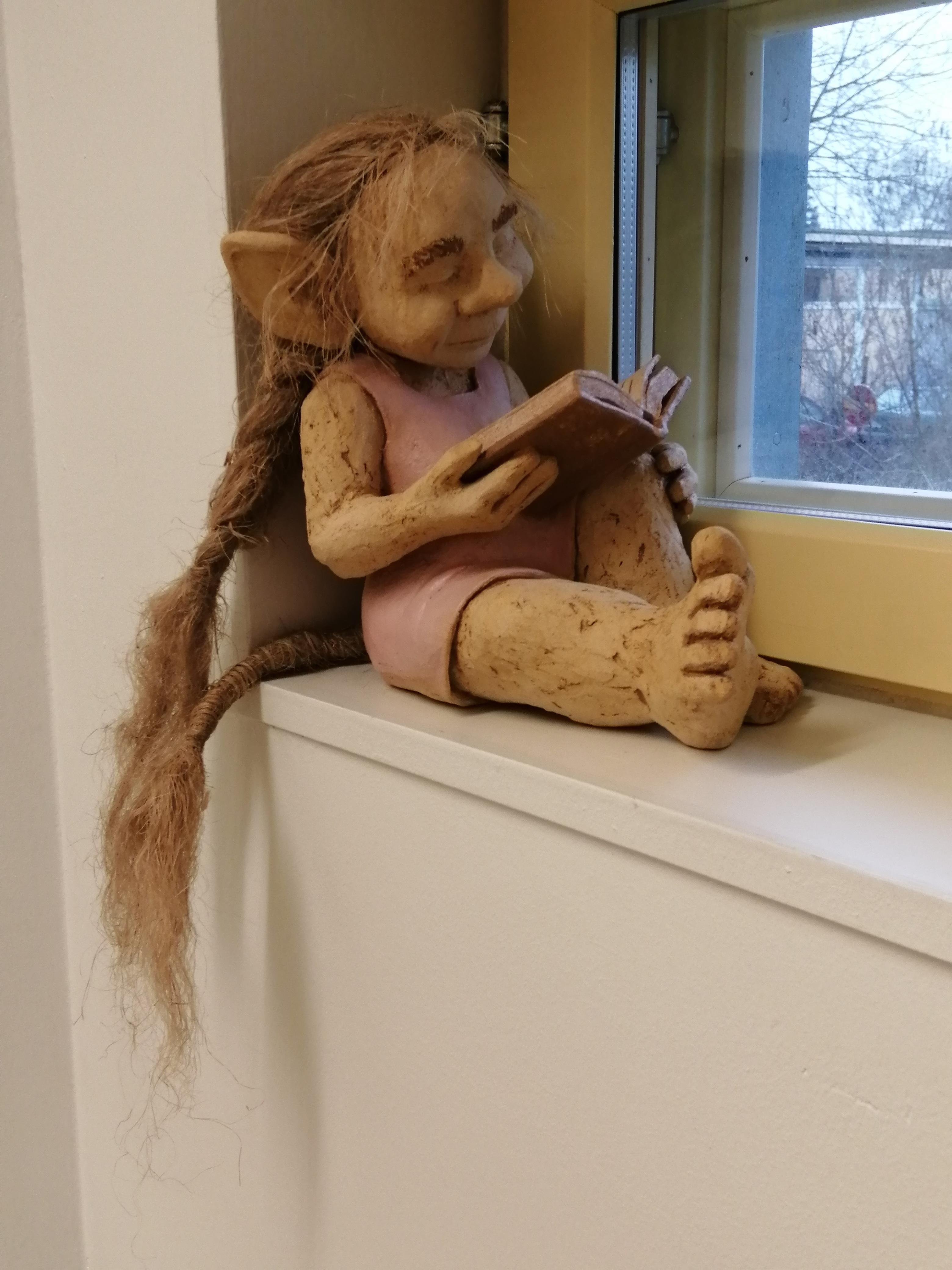 Peikkotyttö ikkunalaudalla lempikirjansa parissa