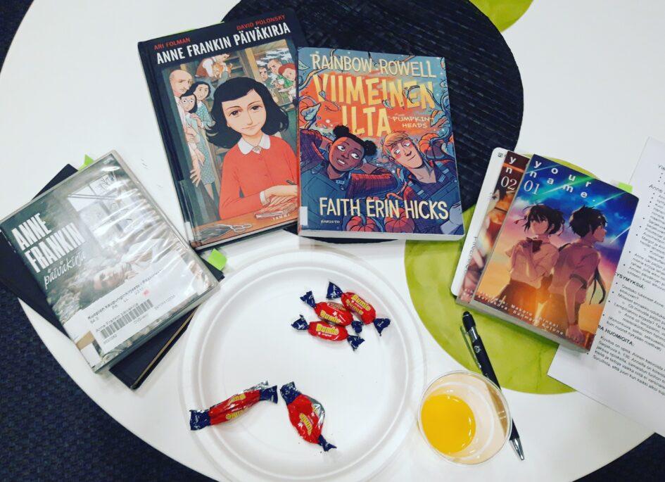 Pöydällä DVD-elokuva ja kirjoja, lautanen jossa Dumble-karkkeja, muki jossa keltaista limonadia, kynä sekä lukupiirin muistiinpanoja.